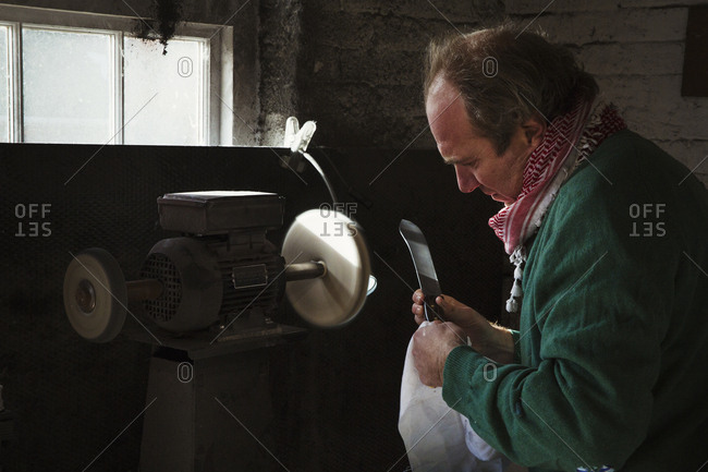 Craftsman in a workshop, holding a knife with a large blade inspecting it, and preparing to use a surface grinder