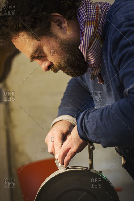 Close up of a craftsman in a workshop, holding the steel blade of a knife on a rotating sanding wheel or grinder