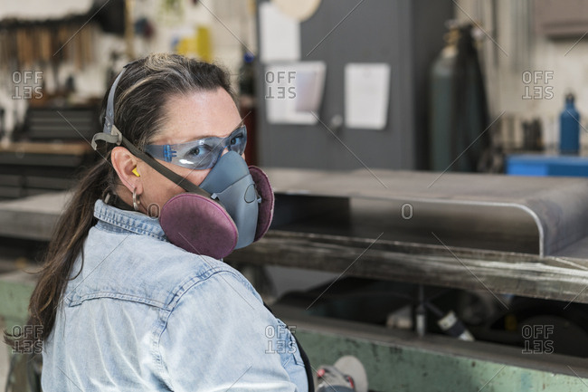 Woman wearing safety glasses and dust mask standing in metal workshop, looking at camera