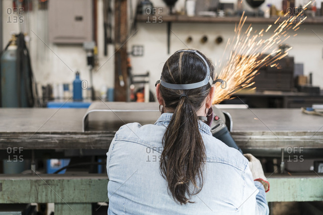 Rear view of woman wearing safety glasses and dust mask standing in metal workshop, using power grinder, sparks flying