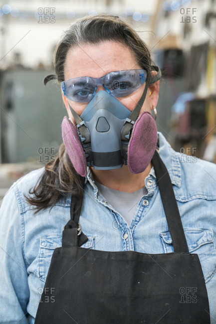 Portrait of woman wearing safety glasses and dust mask standing in metal workshop, looking at camera