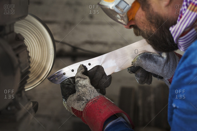A craftsman in a workshop holding a newly milled piece of steel with thick gloves, and smoothing and finishing the end with a surface grinder Wearing protective goggles