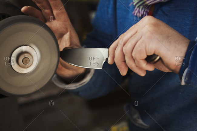Close up of a craftsman's hands, holding a strong steel knife blade against a surface grinder, hand finishing a kitchen knife