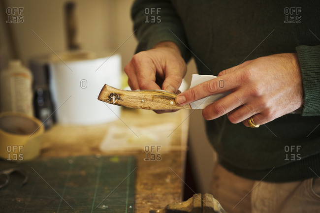 Close up of a craftsman fixing a smooth shaped wooden handle onto a newly made knife blade