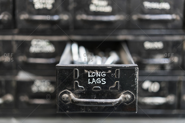 Close up of black metal drawers containing selection of hardware for metal work