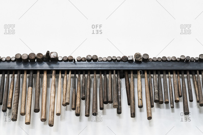 Close up of a selection of hammers hanging on a wall in a metal workshop