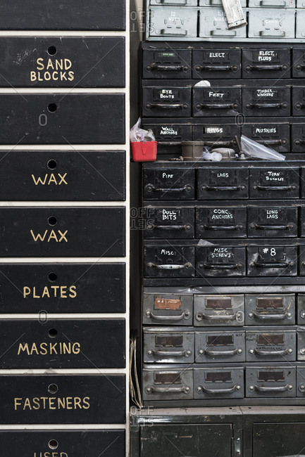 Close up of stack of metal drawers containing selection of hardware for metal work