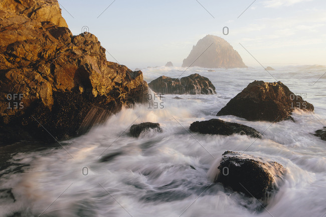 Seascape with breaking waves over rocks at dusk
