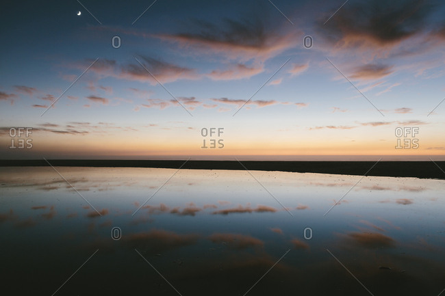 Seascape with dramatic sky reflected in water at dusk