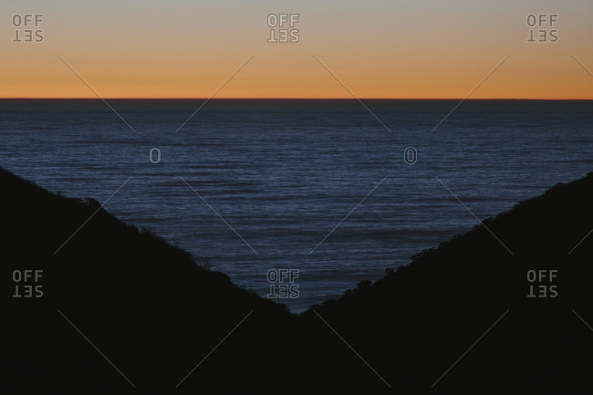 Seascape with ocean at dusk, hills in foreground