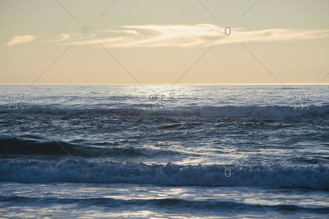 Seascape with breaking waves under cloudy sky at sunset