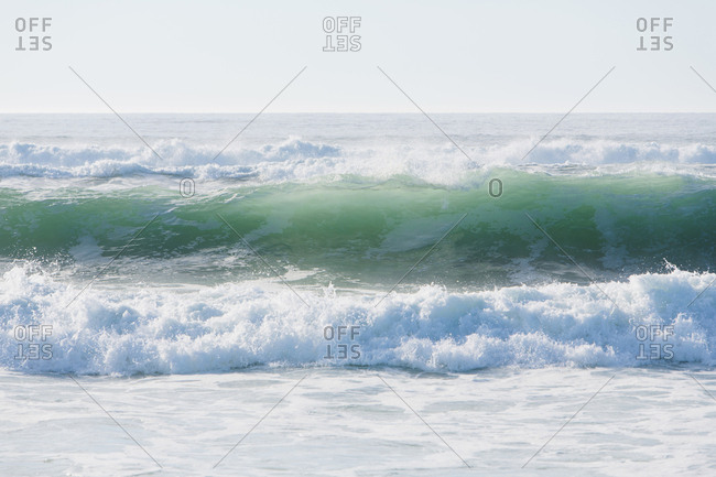 Seascape with breaking waves on sandy beach