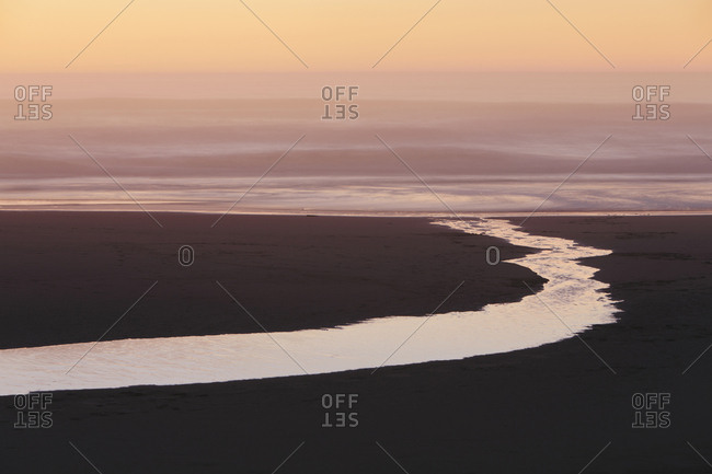 Landscape with small stream flowing into surf at dusk