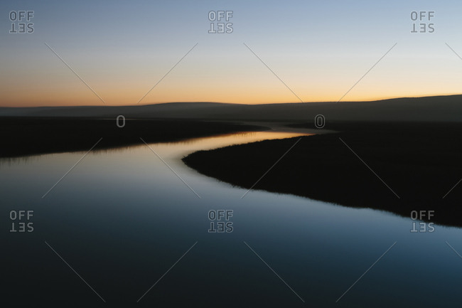 The open spaces of marshland and water channels, flat calm water at dusk