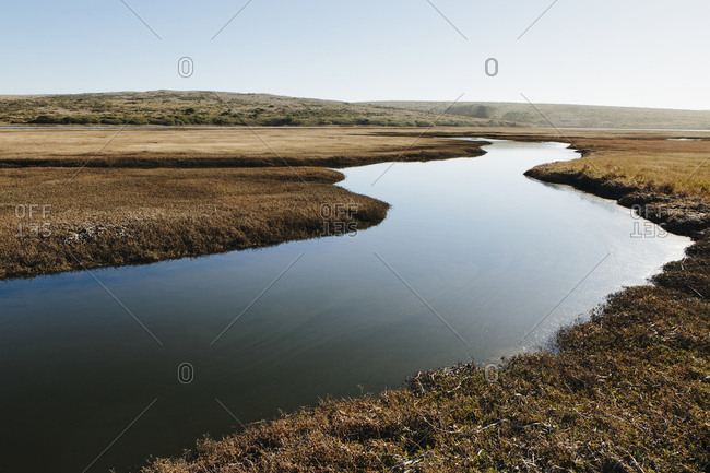 The open spaces of marshland and water channels, flat calm water