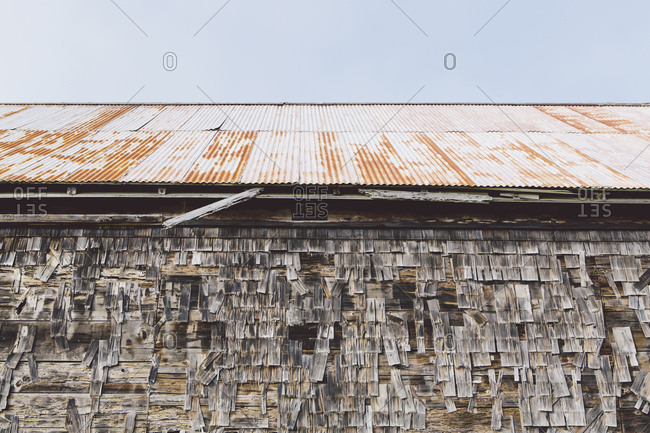 An old farmhouse with wooden shingle tiles on the walls and corrugated iron roof