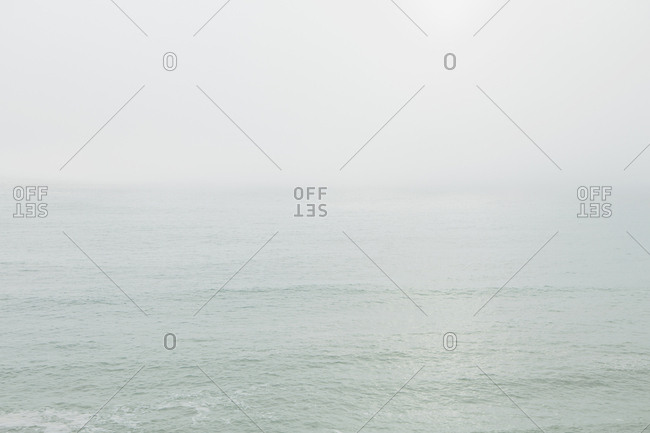 View across the ocean on a calm day, heavy fog in the air