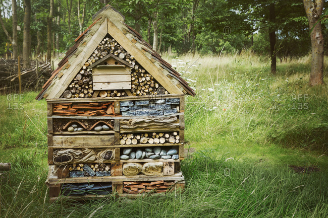 Large bug house with several layers of different materials on a lawn