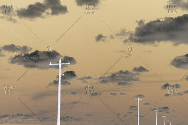 Abstract of power lines and telephone poles extending across cloudy sky
