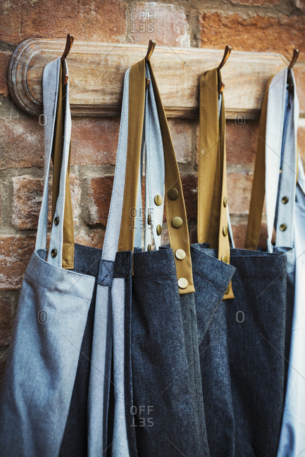Denim work aprons hanging on a row of hooks on a brick wall