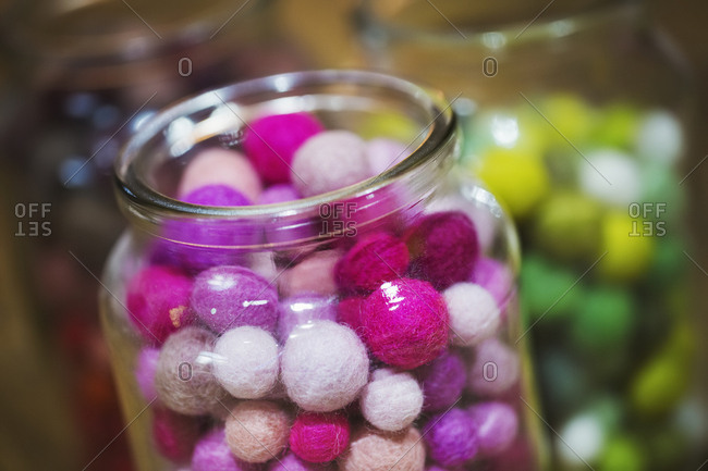 Close up of glass jars with selection of colorful small fabric balls