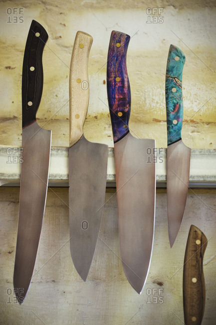 A selection of knives with shaped and painted wooden handles on a magnetic knife holder on a workshop wall