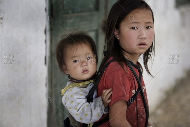 November 24, 2006: Older Children Are Often Main Caregivers Of Their Younger Siblings And Carry Them Around On Their Backs; Sapa, Vietnam