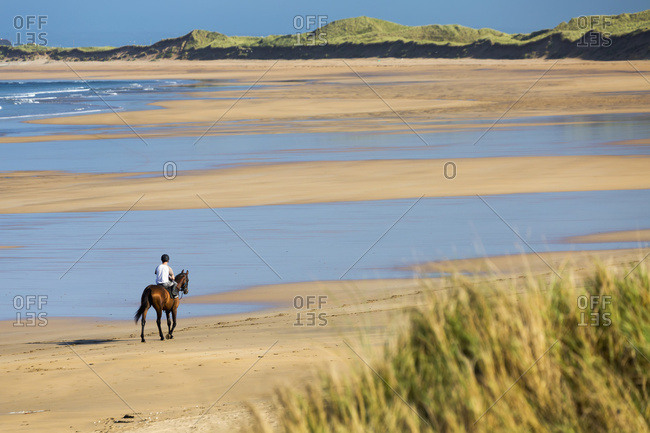September 22, 2014: Horse And Rider On Beach With Grassy Sand Dunes And Blue Sky; Count Clare, Ireland