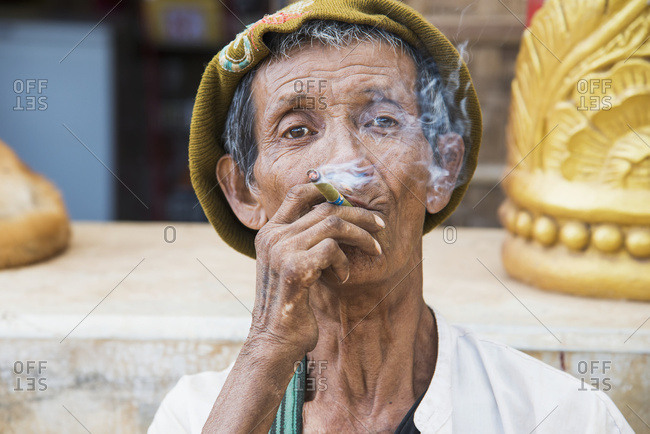 January 2, 2015: A Grizzled Older Man Smokes A Cheroot While Looking Through The Smoke; Myanmar