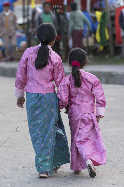 October 18, 2014: Two Young Girls Walking Down A Street Together In Traditional Clothing; Paro, Bhutan
