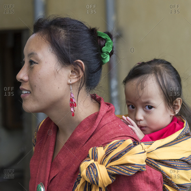 October 15, 2014: A Woman Carrying A Baby Girl On Her Back; Paro, Bhutan
