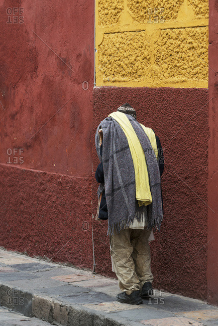 February 1, 2015: A Man Walks Down A Sidewalk Beside A Red And Yellow Painted Building; San Miguel De Allende, Guanajuato, Mexico