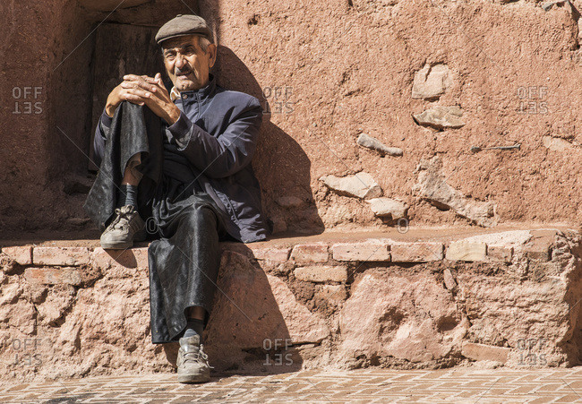 October 31, 2015: Elderly Abyanaki Man Sitting On A Stone Ledge; Abyaneh, Esfahan, Iran