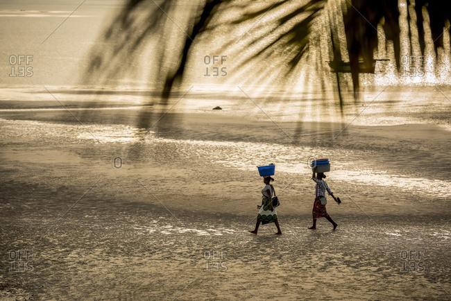 August 27, 2016: Local Women Walking On Vilanculos Beach; Vilanculos, Bazaruto Archipelago, Mozambique
