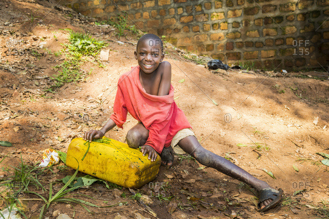 July 5, 2014: A Young Boy Smiles For The Camera While Crouching On The Ground; Uganda