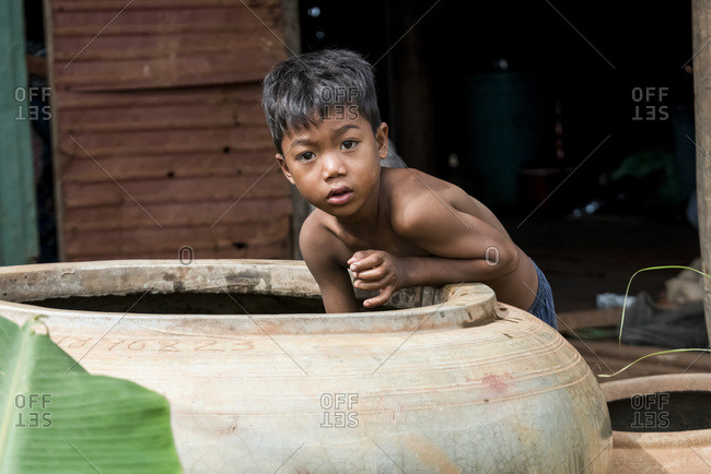 December 19, 2016: A Young Boy Looks At The Camera While Hanging Into A Large Container; Seim Reap, Cambodia