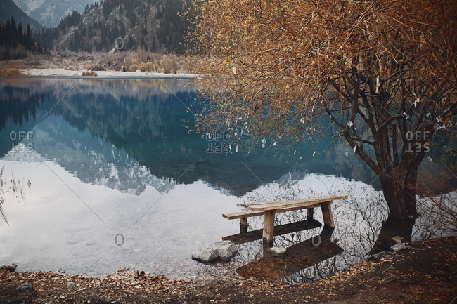 Flooded bench at the mountain lake and fortune wishing tree