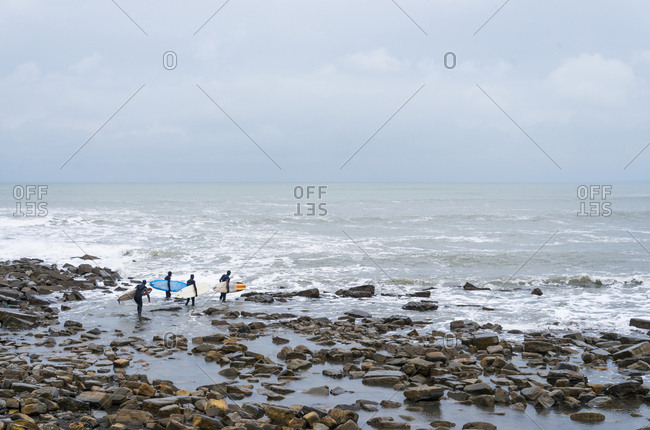Four male surfers carrying their longboards make there way over the rocks towards the sea in Kimmeridge Bay which is located along the Jurassic coastline of Dorset, UK.