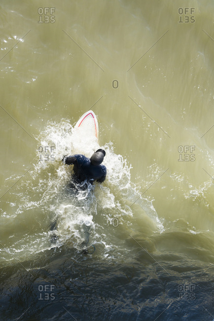 An aerial view of a surfer laying on his board in the sea. he is wearing a thick winter wetsuit with hood.