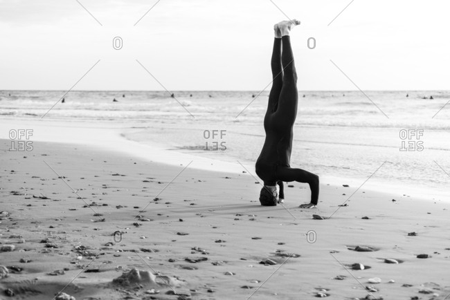 A male surfer performs a yoga headstand on the beach before going in the sea to surf.
