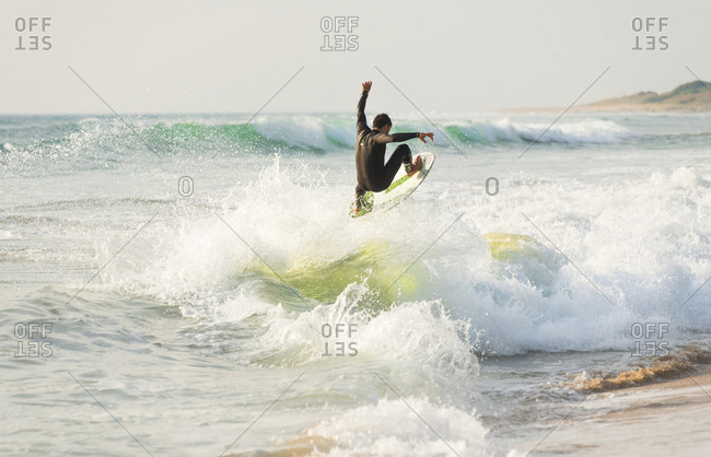 October 21, 2016: A surfer performing a spectacular trick on a wave at Zahora beach in Southern Spain.