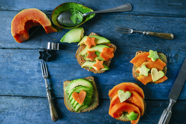 Toast with avocado and papaya on old blue wooden table