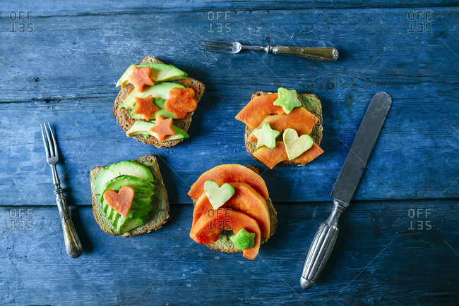Breads with guacamole and papaya on old blue wooden table