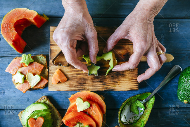 Woman's hands slicing avocado in a star shape for breads with avocado and papaya