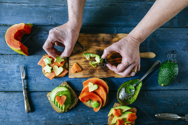 Woman's hands preparing breads with avocado and papaya