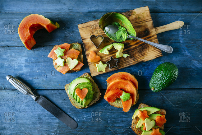 Breads with avocado and papaya on old blue wooden table