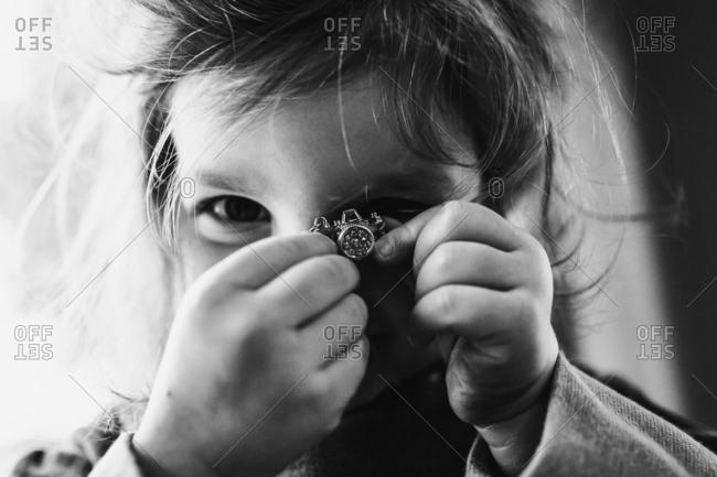 Little girl holding tiny camera
