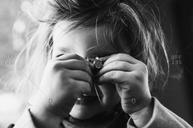 Little girl holding tiny camera in black and white