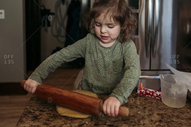 Girl rolling dough for making hamantaschen