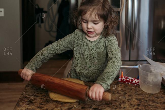 Girl rolling dough for making hamantaschen